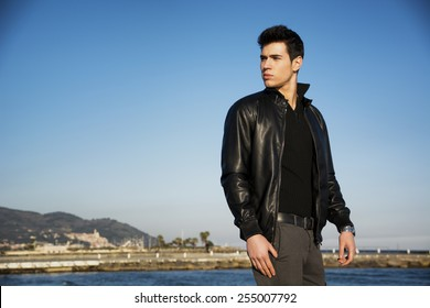 Handsome fashionable young man at the seaside along the shore overlooking the ocean or sea with his black leather jacket looking at the camera