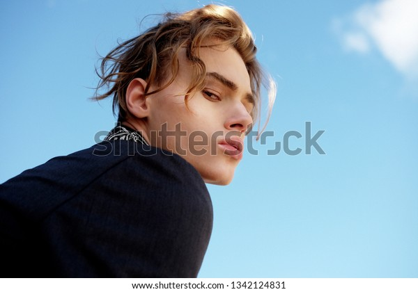 handsome fashionable young man in a suit posing outdoor