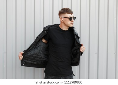 Handsome fashionable young man with sunglasses puts on a denim jacket. Black style