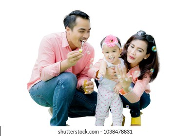 Handsome father and beautiful mother playing soap bubbles with daughter isolated over white