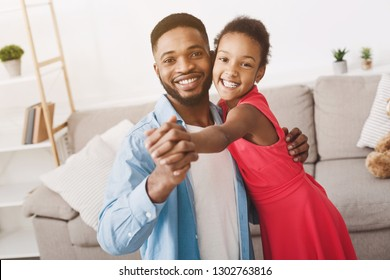 Handsome father and cute daughter dancing at home, looking at camera and smiling