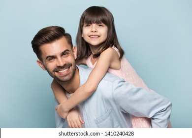 Handsome father give piggyback daughter, holding on back adorable preschool kid pose look at camera isolated on blue background. Playful people having fun, concept of loving family leisure activities