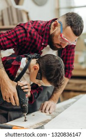 Handsome father and his little pre-teen son dressed in checkered shirts and wearing protective glasses working with drill perforating wood plank at workshop
