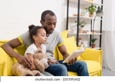 handsome father and little daughter reading book together at home