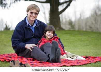 Handsome father sitting at park with disabled son