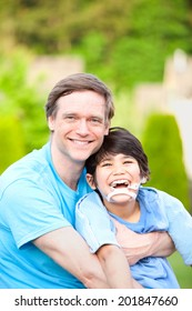 Handsome father sitting with smiling disabled seven year old son outdoors