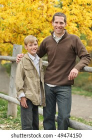 handsome father and son standing together outdoors in fall