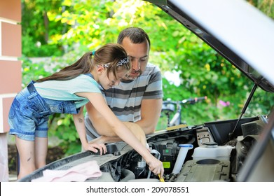 Handsome father teaching his  school age daughter to change motor oil in there family car.