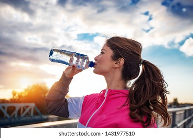 Handsome female athlete drinking water