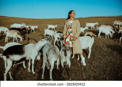 Handsome female shepherdess stands in a pasture among a herd of goats.