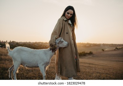 Handsome female shepherdess stands in a pasture near goat and embraces it at sunset.