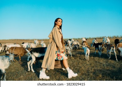 Handsome female shepherdess walks in a pasture among a herd of goats.