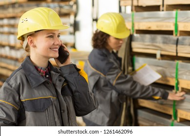 Handsome female worker wearing in gray uniform and yellow hardhat, smiling and speaking on mobile phone in warehouse, while her colleague checking shelves with yellow clipboard on background.