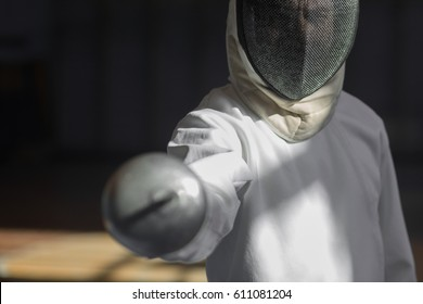Handsome fencer prepares for competitions and a training. Fencer stand with sword and mask. Fencer with sword. Men with sword. Young fencer motivates fencing. Training. Motivation. Swordsman in a mask