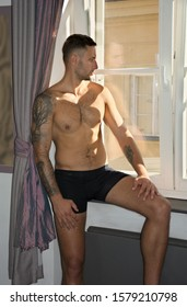 Handsome fit athletic young man shirtless, sitting and looking out of  window