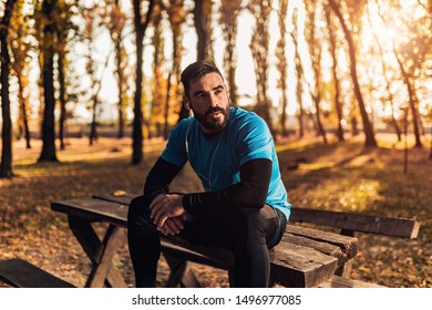Handsome fit man looking in the sky after running in the forest.He has earphone and listening music.