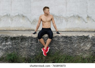 Handsome fit man posing outdoors on grey background