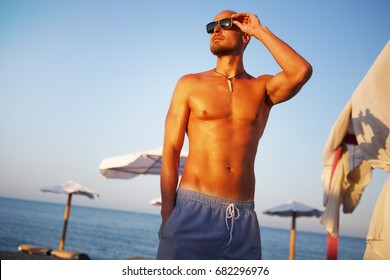 Handsome Fit Man Seaside. Hot Male Sunbathing. Summer pose. Healthy Fitness Male at the Beach