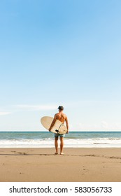 Handsome fit man stand with long surf surfing board wait for wave on surf spot at sea ocean beach. View from back. White blank surfboard. Concept of sport, freedom, new modern life, generation Y.