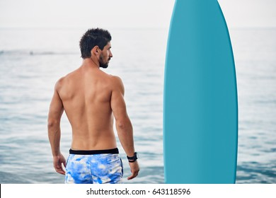 Handsome fit man stands with blue blank surfboard waiting for wave on surf spot at sea beach. View from back.