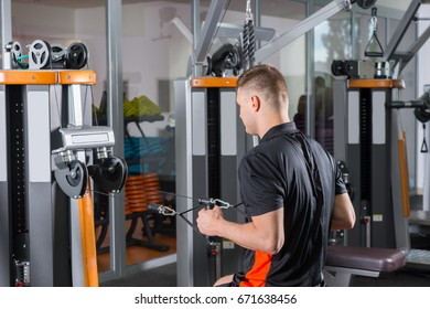 Handsome fit man training on row machine in gym room in fitness center