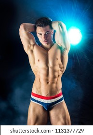 Handsome, fit, muscular young man wearing only underwear standing on grey background, looking down
