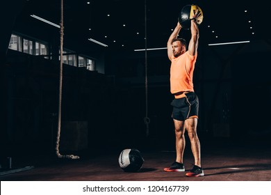 handsome fit sportsman standing with medicine ball overhead in dark gym