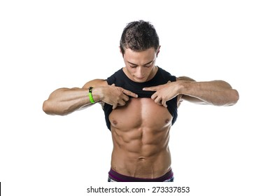 Handsome, fit young man pulling up t-shirt revealing abs. Isolated on white background