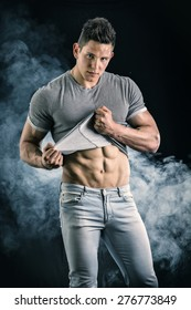 Handsome, fit young man pulling up t-shirt revealing abs. On dark background with smoke