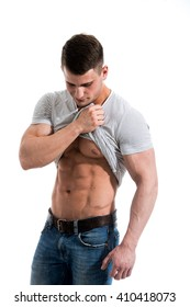 Handsome, fit young man pulling up t-shirt revealing abs. On isolated white background. Studio shot.