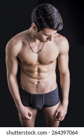 Handsome, fit young man wearing only underwear standing on black background, looking down
