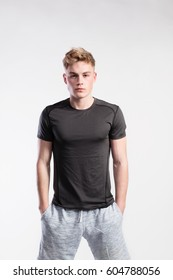 Handsome fitness man in black t-shirt and shorts, studio shot.