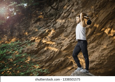 Handsome fitness man posing while doing workout in wild nature environment.