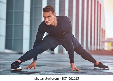 A handsome fitness man in a sportswear, doing stretching while preparing for serious exercise in the modern city against a skyscraper.