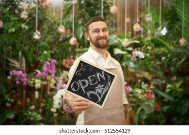 Handsome florist holding board with inscription OPEN