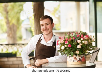 Handsome florist man with fresh flowers on a shop background. Florist business concept. Copy space.