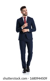 handsome formal man wearing navy suit walking while holding hand on sleeve's button and looking away serious on white studio background