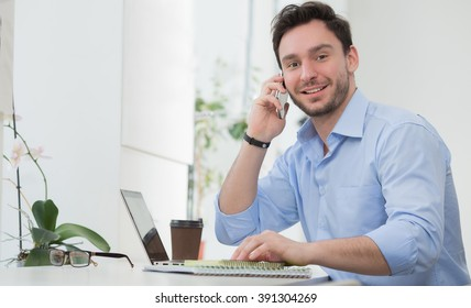 Handsome freelancer speaking over mobile phone with his partners about different business projects in resrtaurant or cafe.