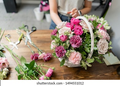 Handsome fresh bouquet. Flowers delivery. Woman florist create flower arrangement in a wicker basket. Beautiful bouquet of mixed flowers. Floral shop concept .