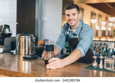 Handsome friendly barista smiling to the camera while putting drip decanter and a glass of coffee on the bar counter
