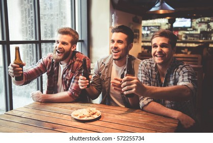 Handsome friends are drinking beer, cheering for sport team and smiling while resting at the pub