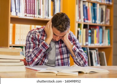 Handsome frustrated student studying his books in library