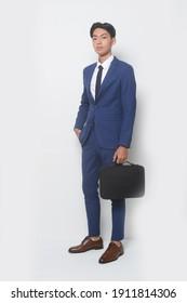 gut aussehender junger Geschäftsmann mit blauem Anzug und Hose, Schuhe, der schwarze Handtasche im Studio hält