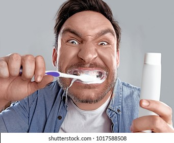 Handsome funny bearded man in whit shirt is obsessed about health of his teeth he cleaned them hard with a toothpaste and a tooth brush and now he is happy