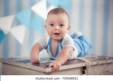 Handsome funny happy baby child boy posing on fur wooden table in blue studio.
