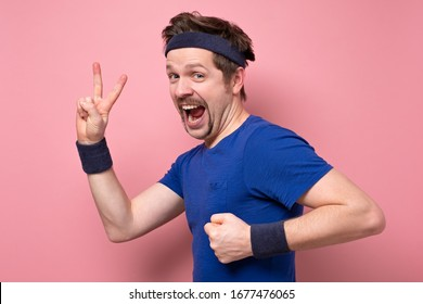 Handsome funny man with funny mustache running fast showing two fingers or victory gesture on pink wall. Sporty lifestyle.