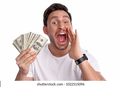 Handsome funny rich Man in white t shirt screams while holding a lot of money in his hand isolated on a white background Guy yelling his secret idia of how to be rich and make millions of dollars