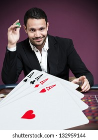Handsome gambler betting on four aces in foreground