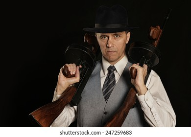 Handsome gangster man in classic suit with guns