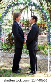 Handsome gay couple holding hands under their floral wedding arch.